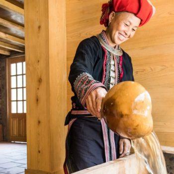 Red Dao woman preparing herbal bath at Topas Riverside lodge in Nam Cang