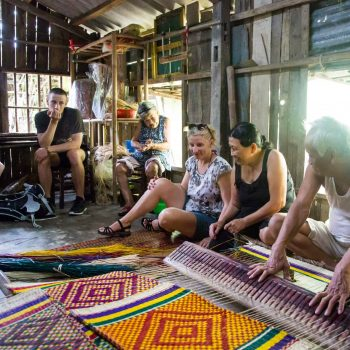 Turists learning local handicraft from Vietnamese in Hoi An