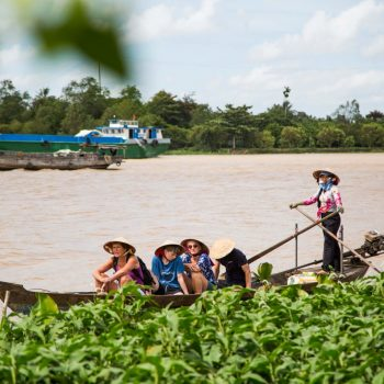 Tourist saling with local guide in mekong river
