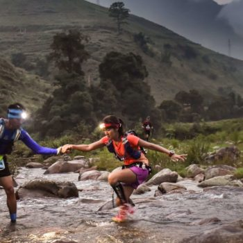Trail runners helping each other cross exotic river in the mist of dawn